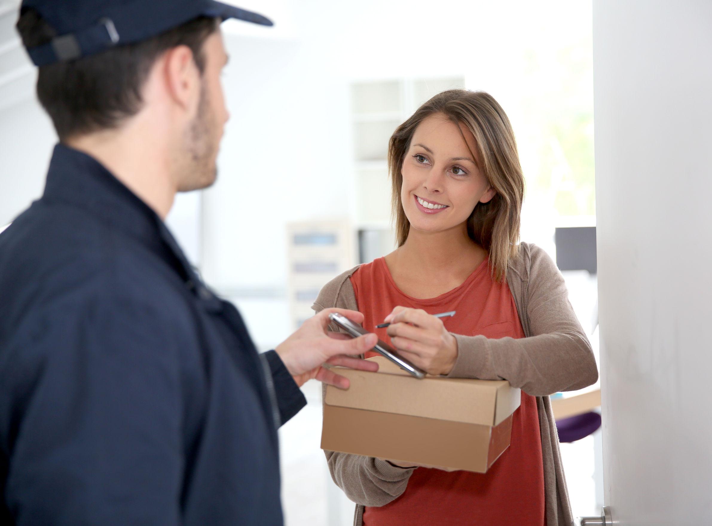 Een vrouw die tekent voor het in ontvangst nemen van haar pakketje.