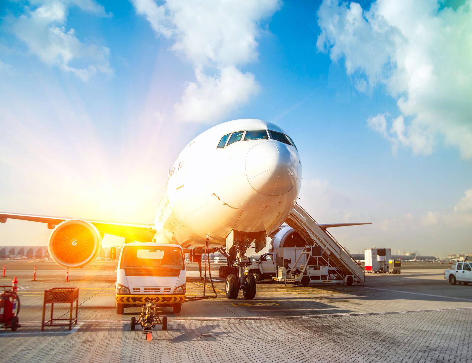 Vliegtuig die klaar wordt gemaakt voor vertrek met opkomende zon.