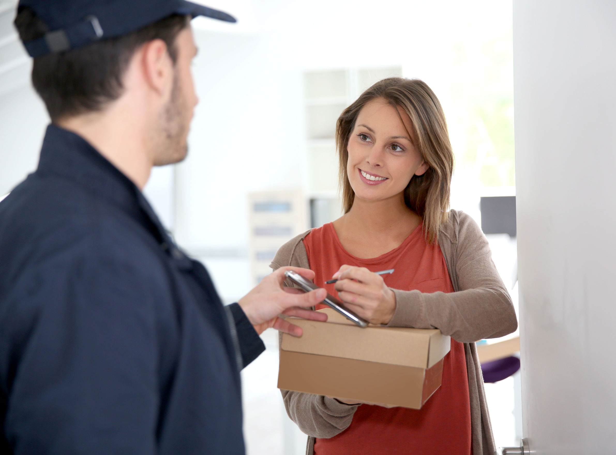 Woman signing to accept and receive her parcel from the carrier